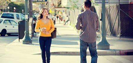 homem e mulher se cruzam na rua e se olham