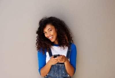 mulher cabelos cacheados sorrindo com celular na mão